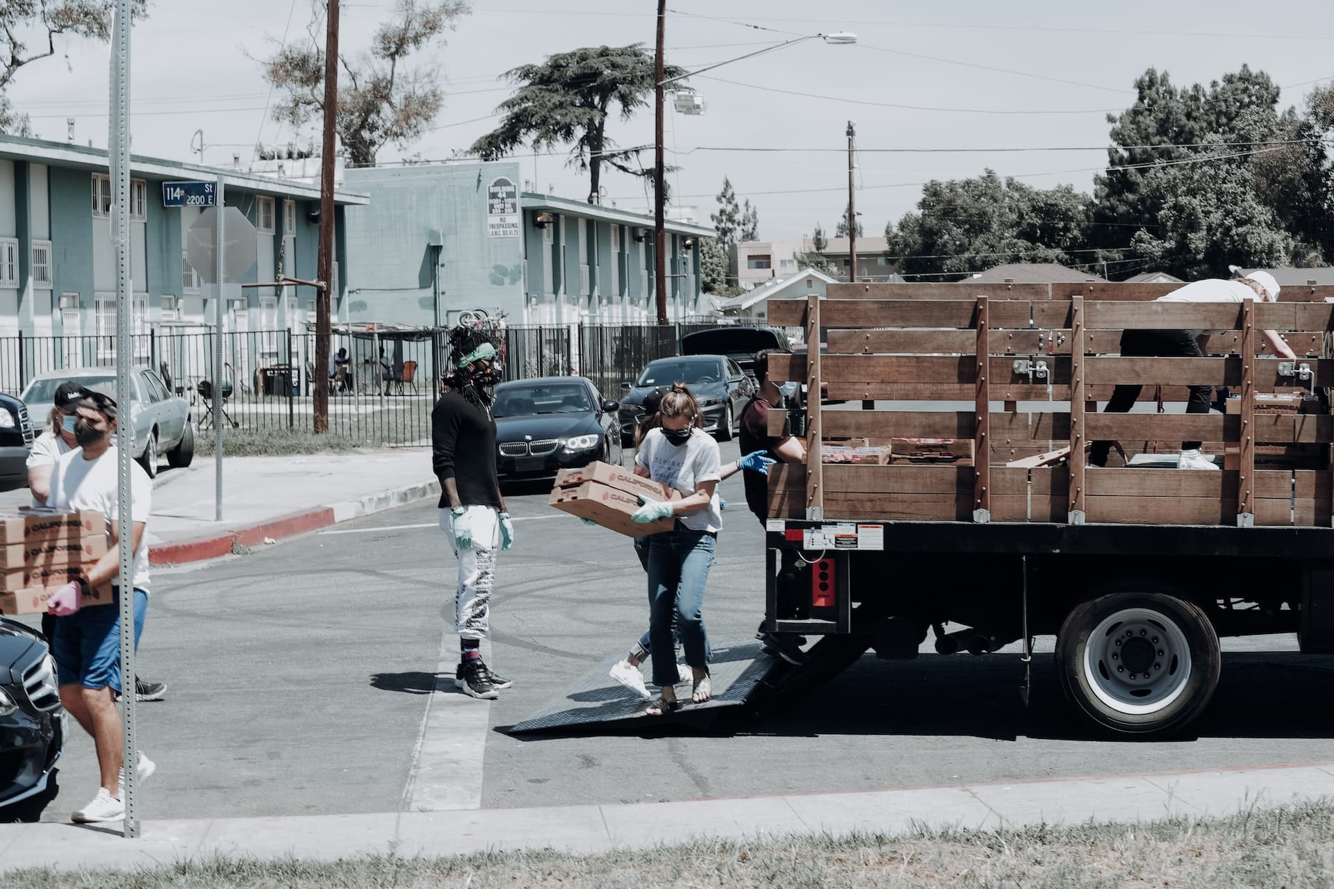 People unloading boxes of food from a truck in the street.
