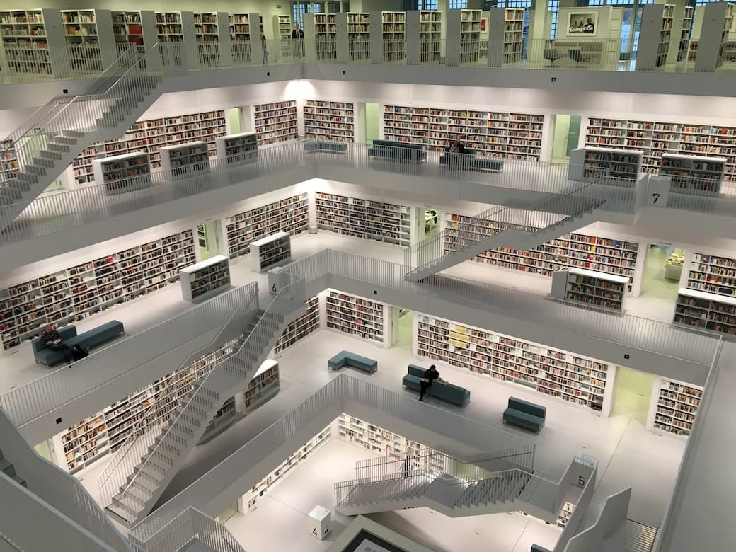 A top down photo of a modern library atrium from the 4th floor looking down on the other floors with books neatly packed onto white shelves.